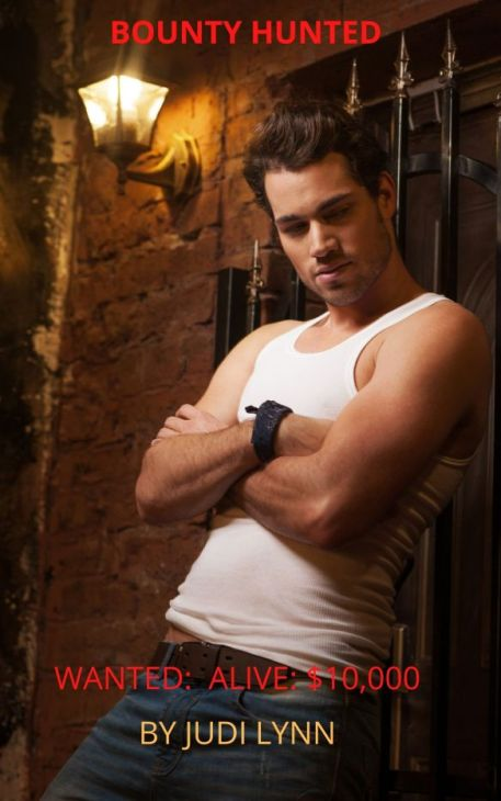 Cover for Bounty Hunted by Judi Lynn shows sexy young man, arms folded, leaning against wall in alley